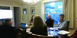 Seven people sitting around a table speaking and listening while a slideshow is playing on a large monitor in the background.