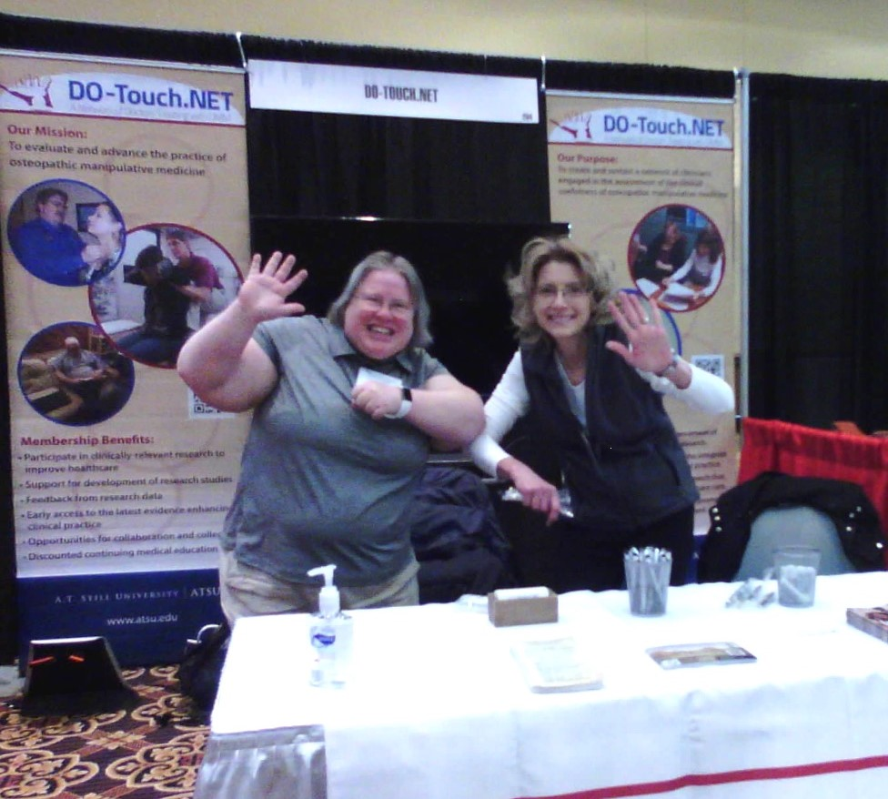 Jane and Lisa waving from behind a display table in the convocation booth for DO-Touch.NET.
